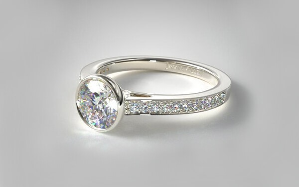 Bezel set engagement ring with pave set white gold band